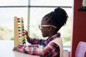 girl using abacus in classroom